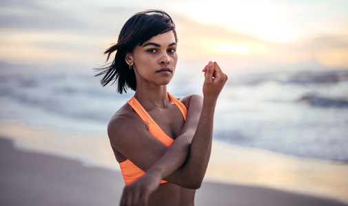 Woman doing warm up exercise at the beach