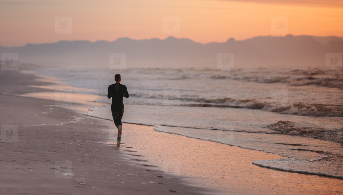 Runner training on the beach in morning