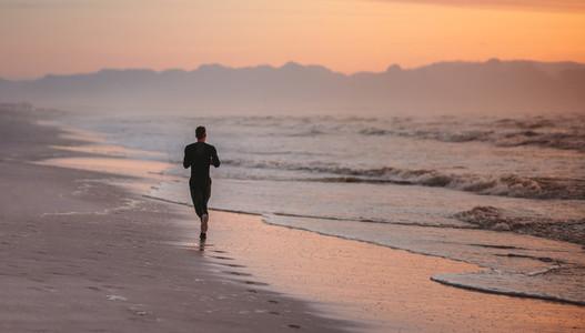 Runner training on the beach in morning