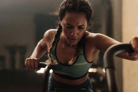 Woman doing intense workout on gym bike