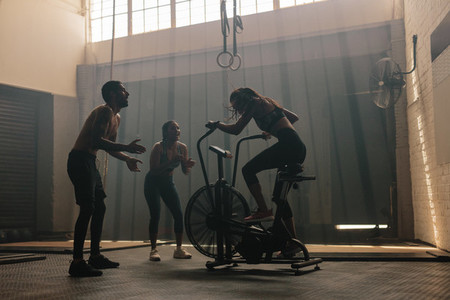Friends motivating woman on exercise bike in gym