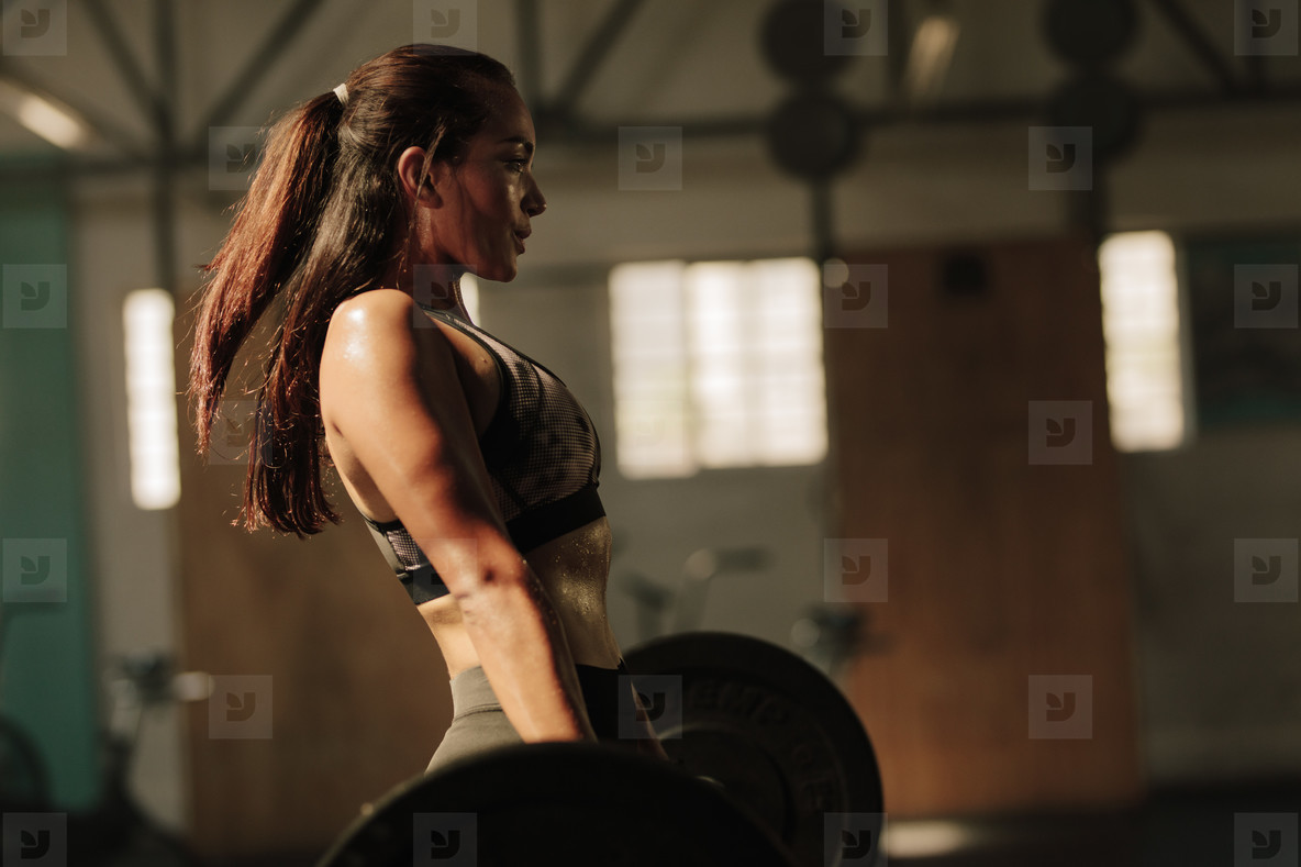 Physically fit woman lifting heavy weights