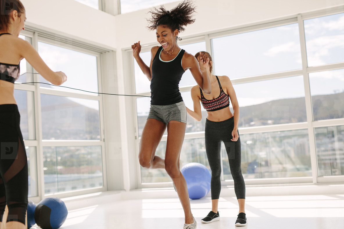 Females enjoying jumping rope workout at gym