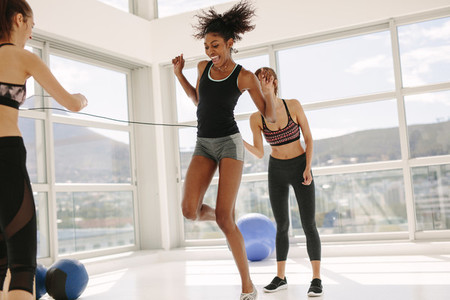 Females enjoying jumping rope workout at gym