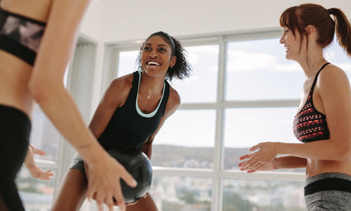 Smiling workout partners exercising with medicine ball