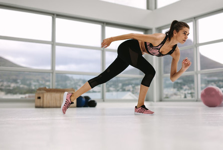 female in a stretching pose at fitness studio