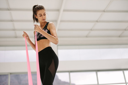 Woman using resistance band for arms exercise