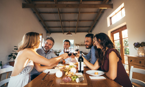Friends having fun with wine and food at home party
