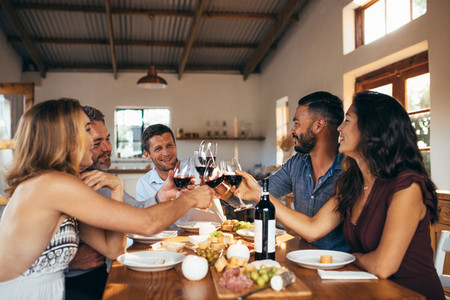 Cheerful friends toasting wine at dinner party
