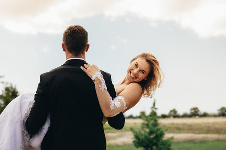 Groom carrying smiling bride on wedding day