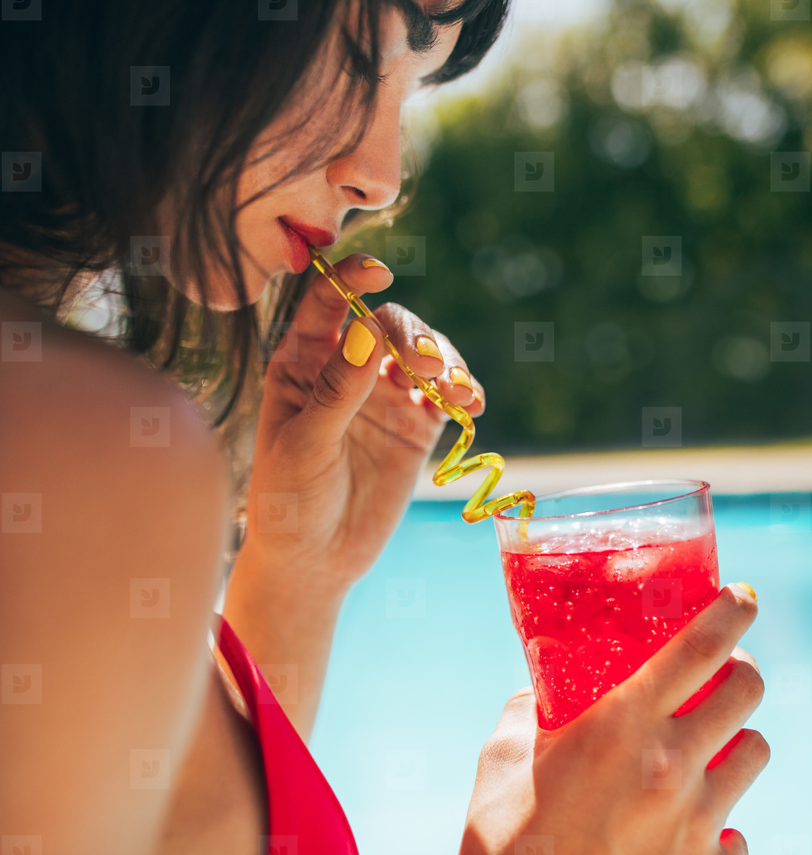Woman drinking cocktail at the poolside