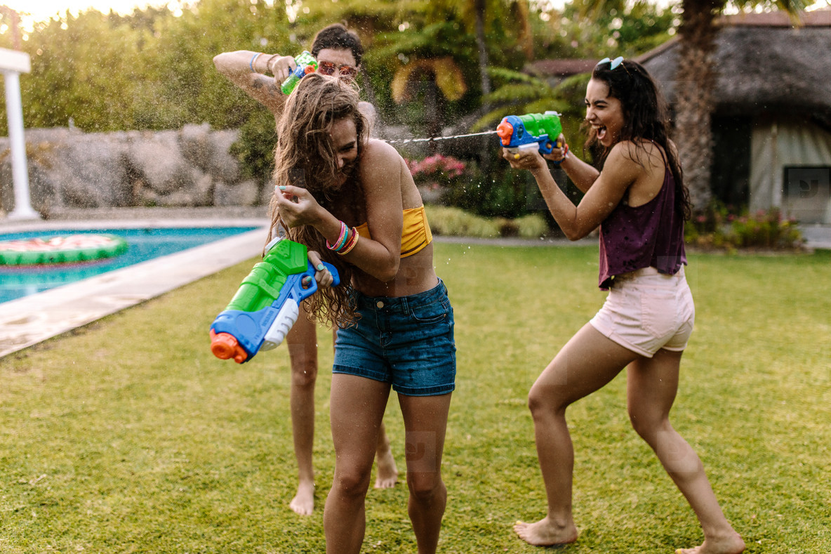 Happy friends doing water gun battle at poolside