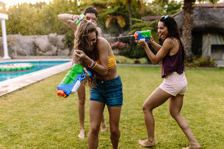 Happy friends doing water gun battle at poolside