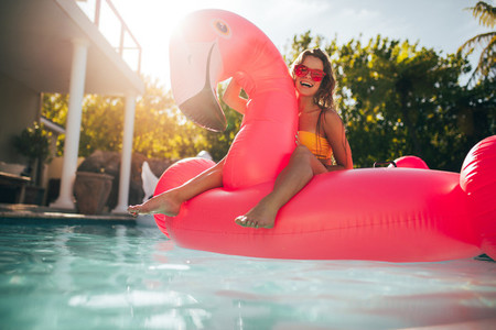 Woman having fun on an inflatable pool float mattress