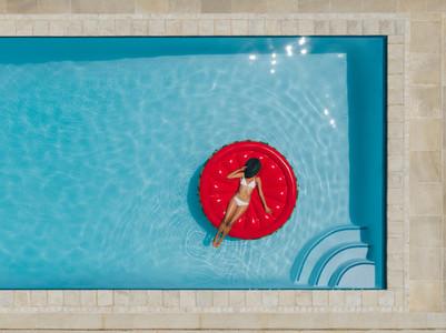 Female sunbathing on floating mattress in pool