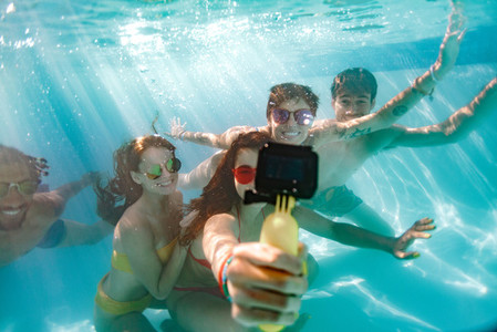 Group of young people taking selfie underwater