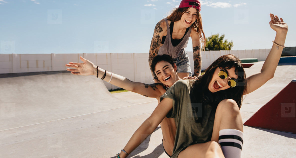 Women at skate park having fun with skateboard