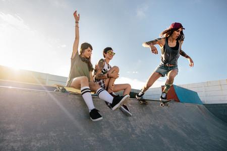 Skateboarding woman riding skateboard at skate park ramp