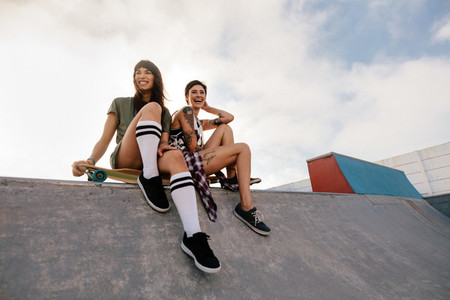 Urban girls in skate park laughing and having fun