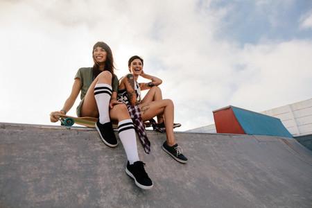 Urban girls in skate park laughing and having fun
