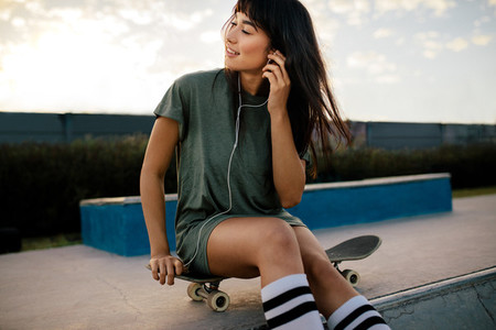 Woman relaxing at skate park listening music