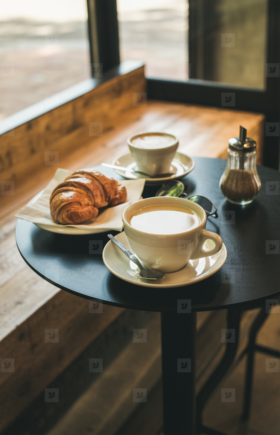 Coffee latte  cappuccino and croissant on small table in cafe