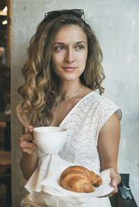 Blond woman sitting with cup of cappuccino and croissant