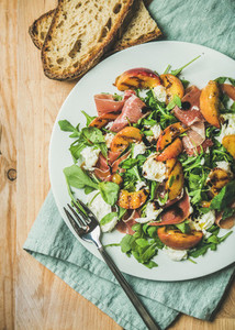 Arugula  prosciutto  mozzarella and grilled peach salad in white plate