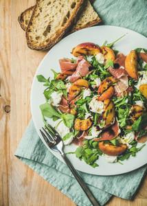 Arugula  prosciutto  mozzarella and grilled peach salad in white plate