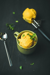 Refreshing Mango sorbet ice cream scoops with fresh mint