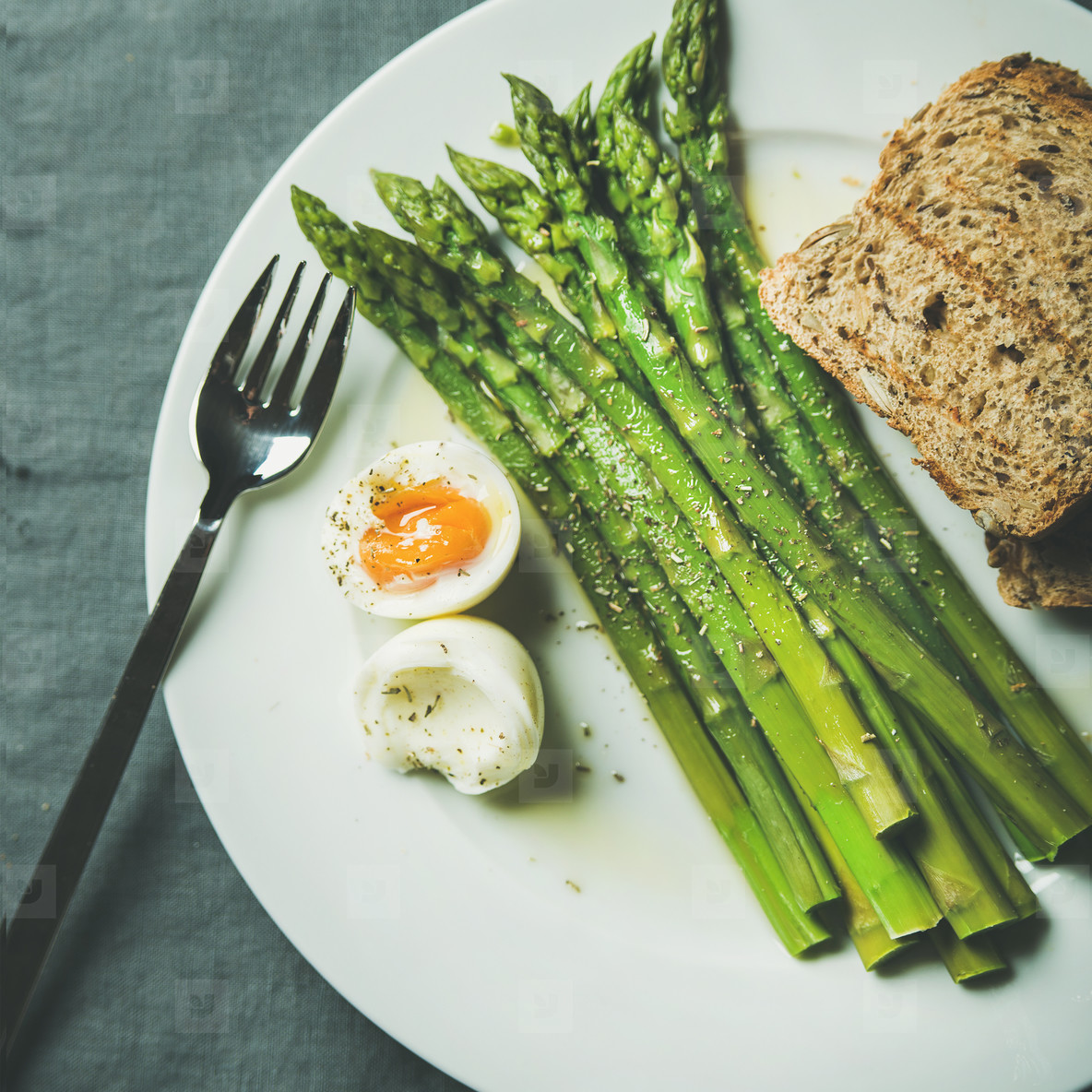 Cooked asparagus with soft boiled egg and grilled bread  square crop