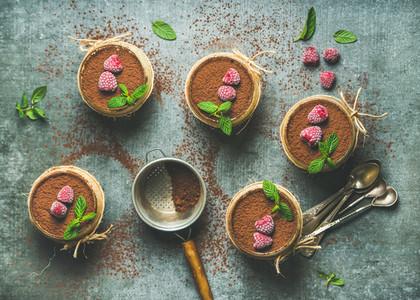 Homemade Tiramisu in individual glasses with frozen raspberries