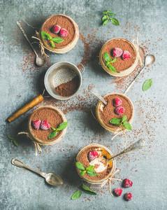Homemade Italian dessert Tiramisu in glasses with fresh mint leaves