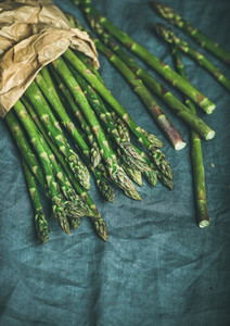 Fresh green asparagus in craft paper bag  copy space