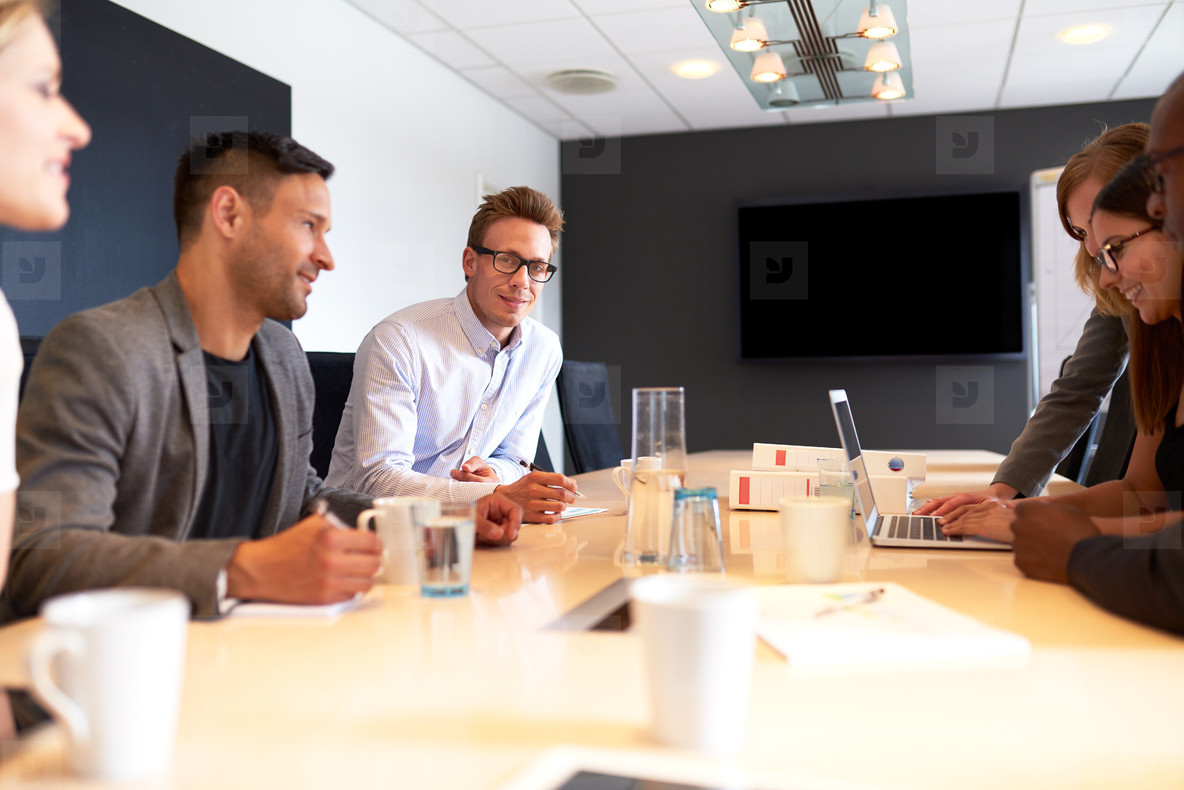 White male executive smiling at camera in work meeting