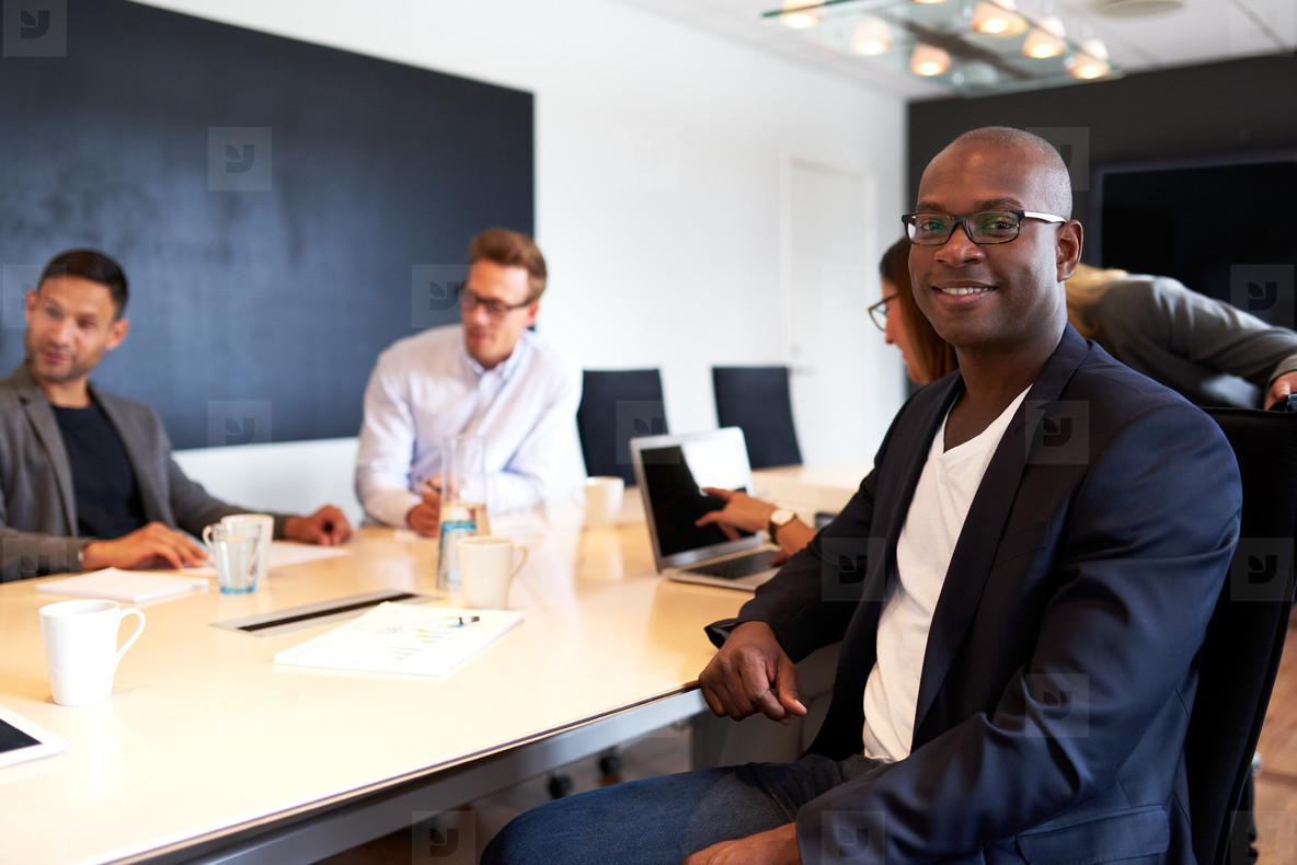 Black male executive facing camera during meeting