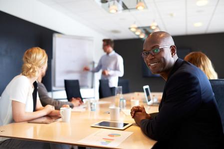 Black male executive smiling at camera during meeting