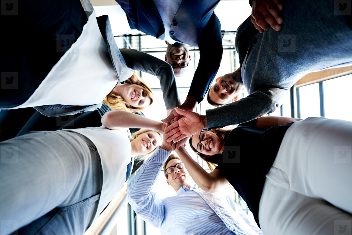 Group of executives looking down hands together