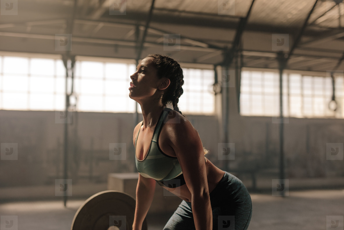 Female athlete lifting weights in gym