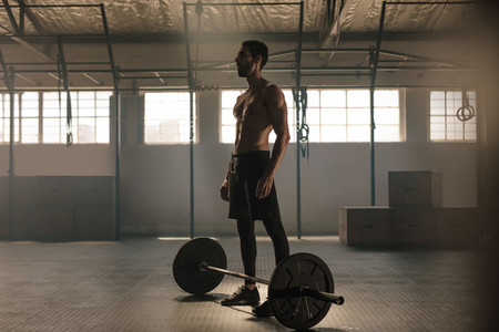 Muscular young man with barbell at gym