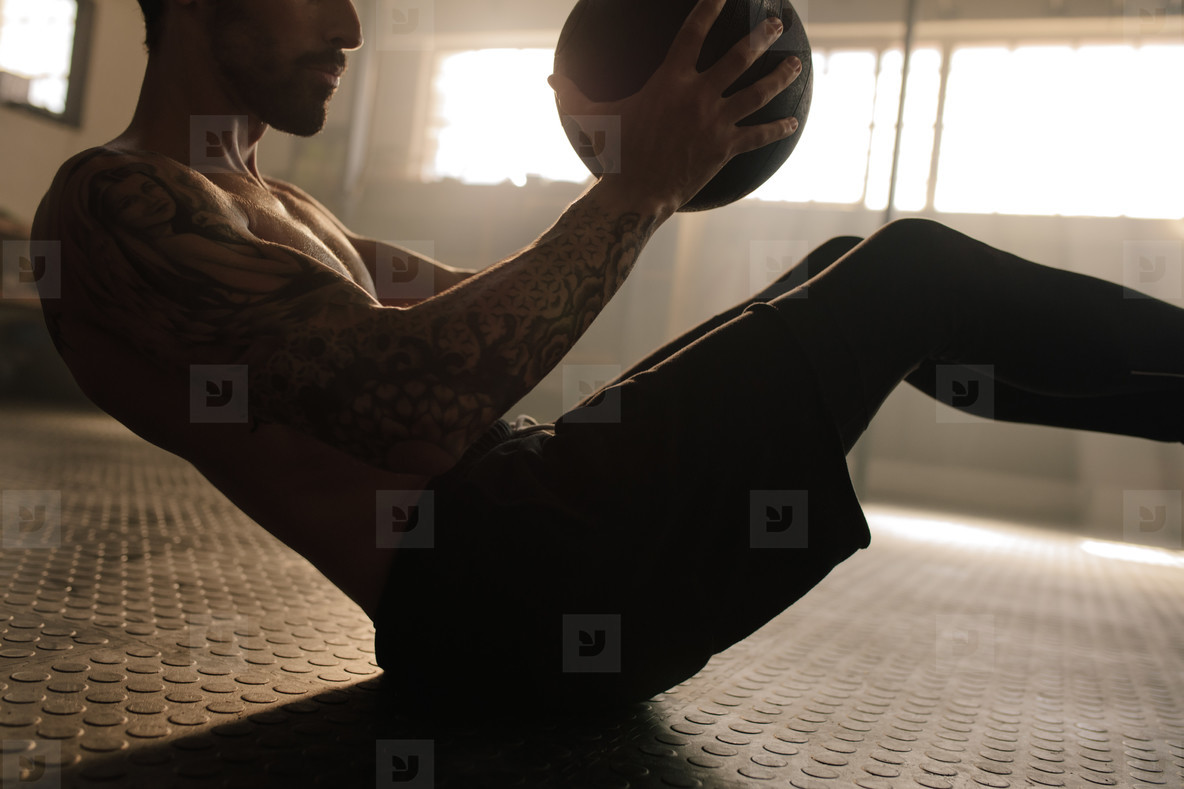 Muscular man exercising with medicine ball at gym