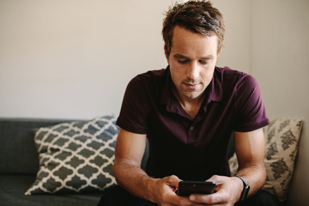 Freelancer looking at mobile phone sitting at home