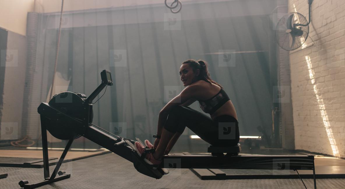 Woman sitting rowing machine at gym