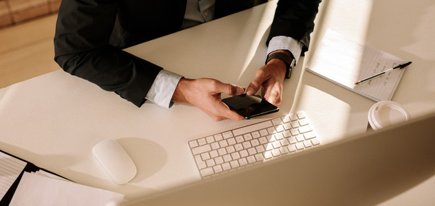 Businessman using mobile phone sitting in front of computer