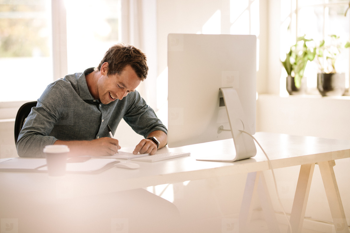 Entrepreneur making notes while working on computer at home