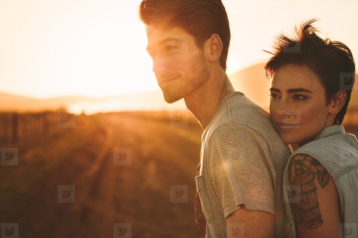 Woman embracing a man outdoors on a road trip