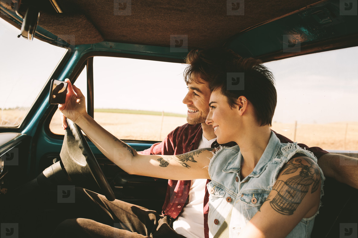 Young couple on a road trip driving in car