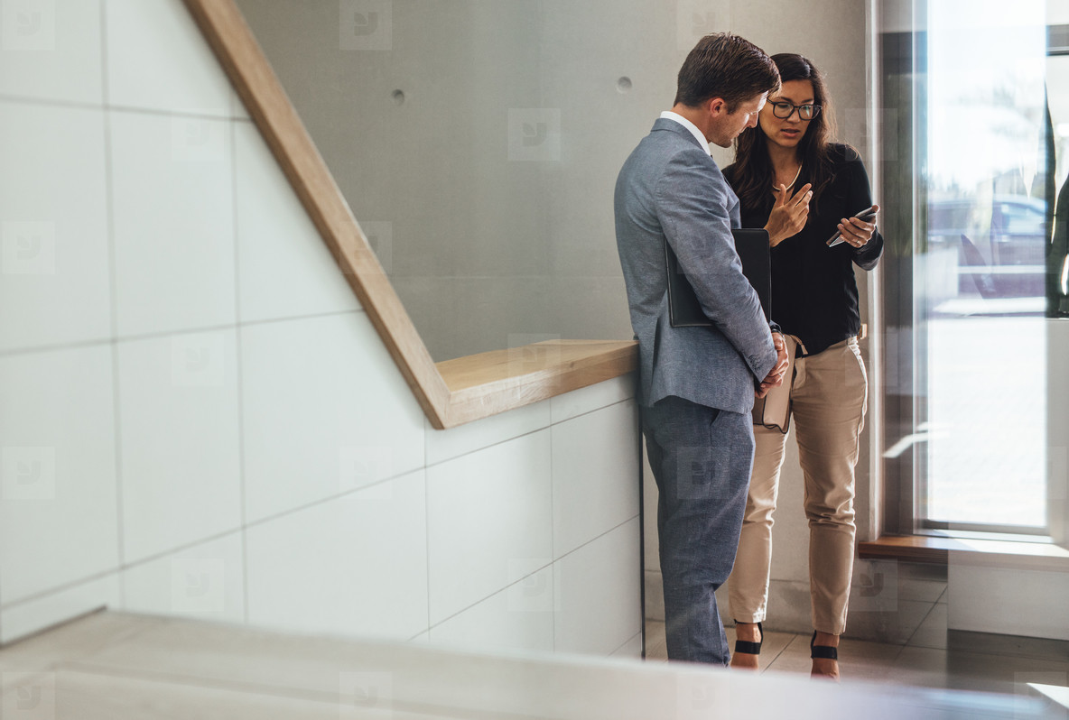 business associates discussing work in office stairway