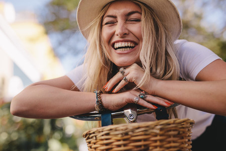 Attractive woman laughing outdoors with her bike