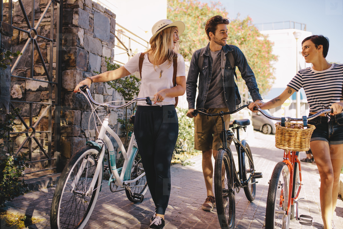 Friends with bikes walking outdoors in city
